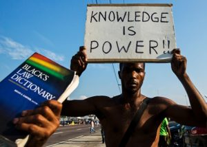 photo black man holding sign knowledge is power