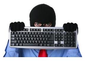 Stock photo man in mask hiding behind computer keyboard