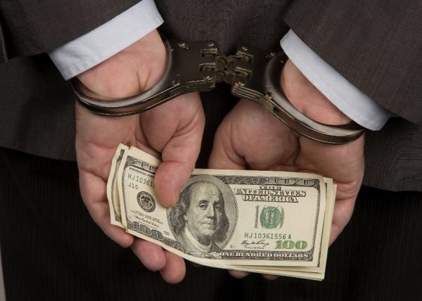 stock photo man handcuffed closeup hands holding money