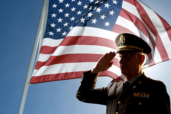 stock photo military veteran saluting with american flag in background